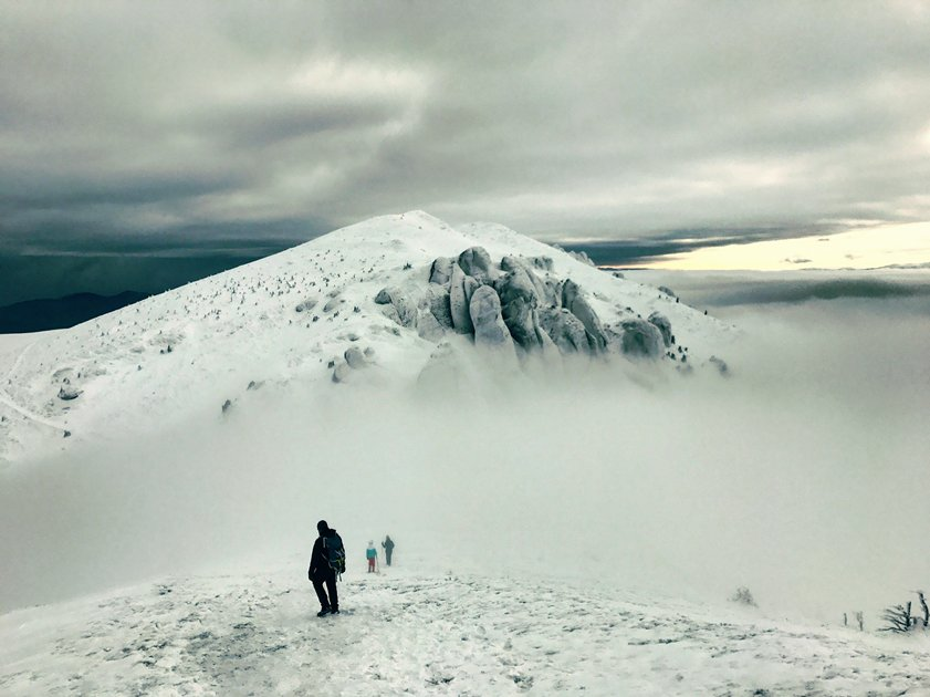 three people trekking in snow